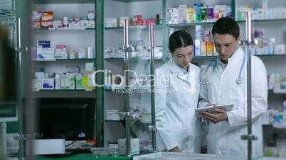 Two pharmacists using digital tablet in pharmacy