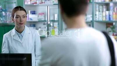Female pharmacist counseling customer in pharmacy