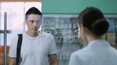 Young male customer buying medicine at pharmacy