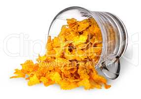 Cornflakes spill out of a glass cup