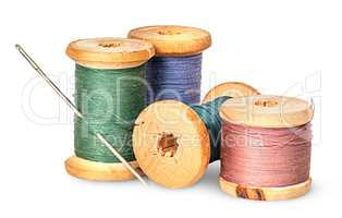 Needle and multicolored thread on wooden spool