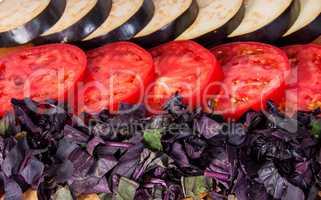 Sliced eggplant tomato and basil leaves horizontally