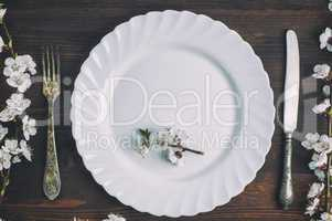 White plate with a fork and knife on a brown wooden surface
