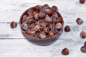 Hazelnuts in a shell in a clay bowl on a white surface