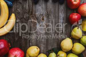 Fresh fruits on a gray wooden surface, bananas, apples, plums an