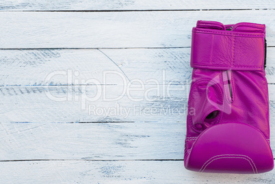 One pink boxing glove on a white wooden surface