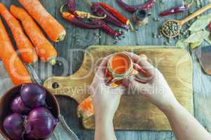 Women's hands hold a jar of carrot juice