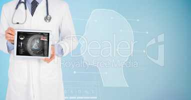 Digitally generated image of male doctor showing digital tablet with human face graphics in backgrou