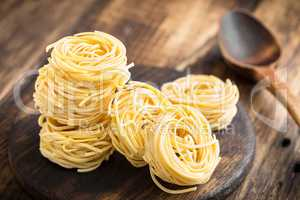 Raw all'uovo pasta, egg noodles on dark wooden rustic background, traditional italian cuisine
