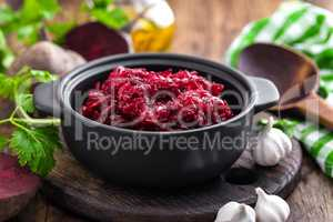 Beetroot salad on wooden background closeup