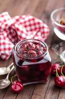 Berries cherry with syrup in a glass jar. Canned fruit