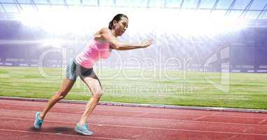 Full length of female athlete running on racing track