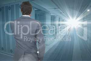 Digital composite image of businessman looking at light at data center