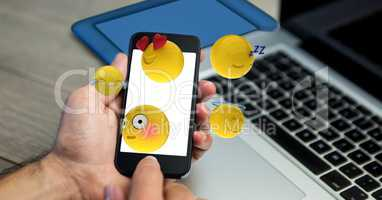 Close-up of hands holding mobile phone with various emojis at wooden table