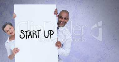 Portrait of smiling business people holding billboard with start up text against gray background