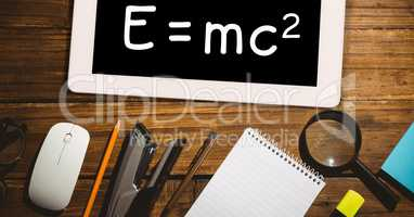 Directly above shot of formula in digital tablet with office supplies on wooden table