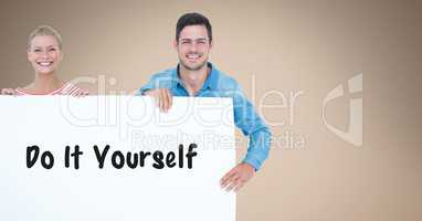 Smiling couple holding bill board with do it yourself text on it