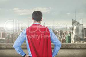 Businessman in super hero costume looking at cityscape