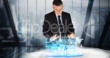 Digital composite image of businessman working on project at desk