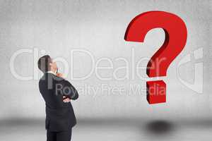 Business man looking question mark against gray background