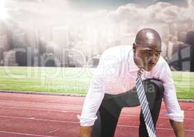 Business man on start line against skyline with clouds and flare