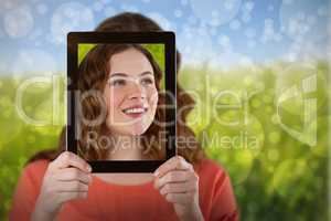 Composite image of woman holding digital tablet in front of her face