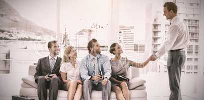 Businessman shaking hand with woman sitting with people waiting for interview