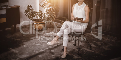 Full length of businesswoman using digital tablet while sitting on chai