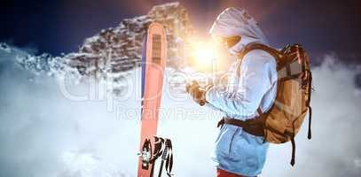 Composite image of skier with skis and backpack using mobile phone