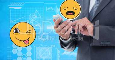 Digitally generated image of businessman using smart phone with emoji tech graphics