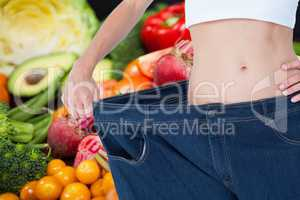 Midsection of woman wearing loose jeans with fruits and vegetable in background representing weight
