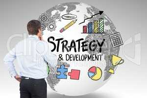 Rear view of businessman looking at strategy and development icons on globe