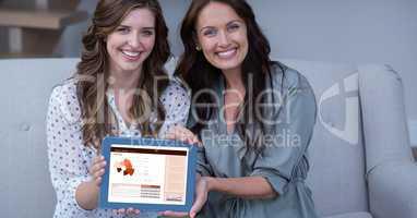 Happy businesswomen showing plan on digital tablet