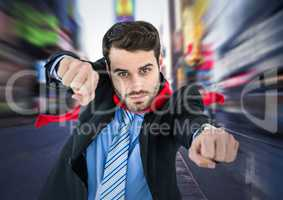 Business man superhero with hands out against blurry street