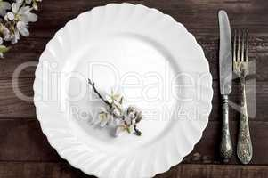White dish with iron cutlery on a brown wooden surface
