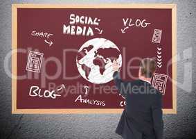 Business man drawing on a blackboard the earth and a social media graphic