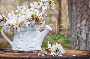 bouquet of flowering almond branches in a white vase on a tree s