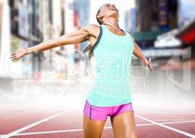 Female runner on track against blurry city
