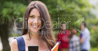 Portrait of smiling female collage student with math's equations on transparent screen