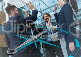 Business team high fiving and compass graphic