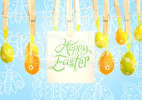 Happy Easter text with Easter Eggs with note on pegs in front of pattern