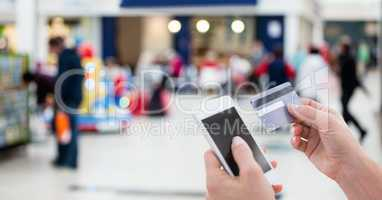 Cropped image of person using smart phone for paying bill through debit card