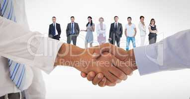 Cropped image of business people doing handshake with employees in background