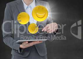 Business woman mid section with tablet and emojis with flare against concrete wall