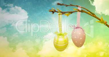 Easter eggs on branch in front of cloudy sky