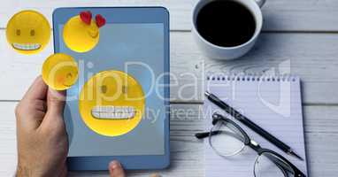 Digitally generated image of emojis flying over hand using digital tablet by coffee cup and eyeglass