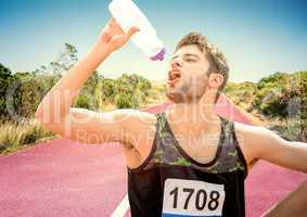 Male runner drinking on track in desert