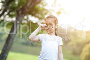 Asian little girl exploring nature with magnifier glass at outdo