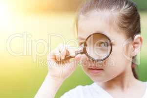 Asian child with magnifier glass at outdoors.