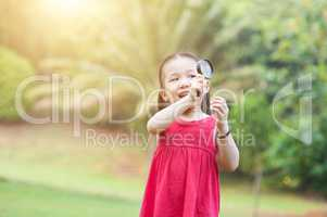 Little girl exploring nature with magnifier glass at outdoors.